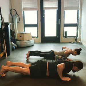 man and woman doing push ups in online exercise class